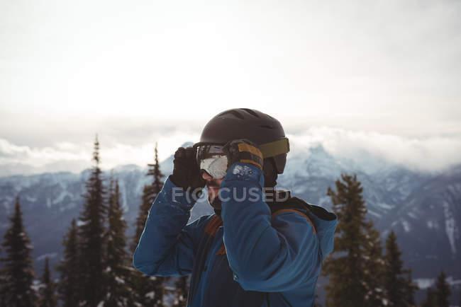 Mann trägt im Winter Helm am Berg gegen den Himmel — Stockfoto