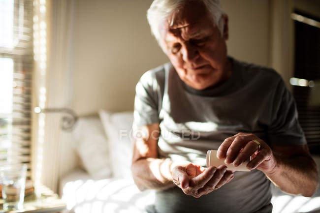 Uomo anziano che prende la medicina in camera da letto a casa — Foto stock