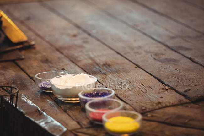 Close-up of frit glass in plastic containers at glassblowing factory — Stock Photo
