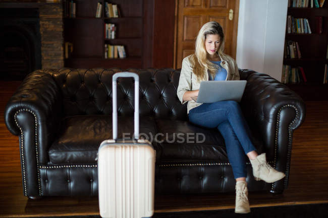 Beautiful woman using laptop in waiting area at airport terminal — Stock Photo