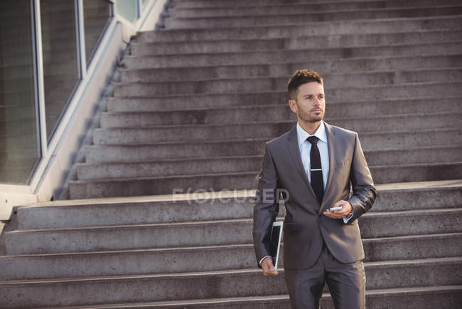Businessman holding mobile phone while walking down steps — Stock Photo