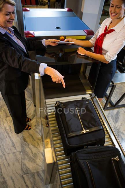 Empresaria señalando equipaje guardado en cinta transportadora en la terminal del aeropuerto - foto de stock
