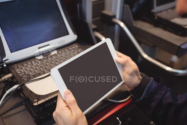 Mani di meccanico in possesso di tablet digitale in garage di riparazione — Foto stock