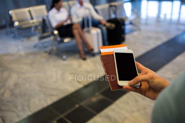 Рука жінка холдингу смартфон, паспорт та інтернатів проходити в аеропорту терміналу — стокове фото