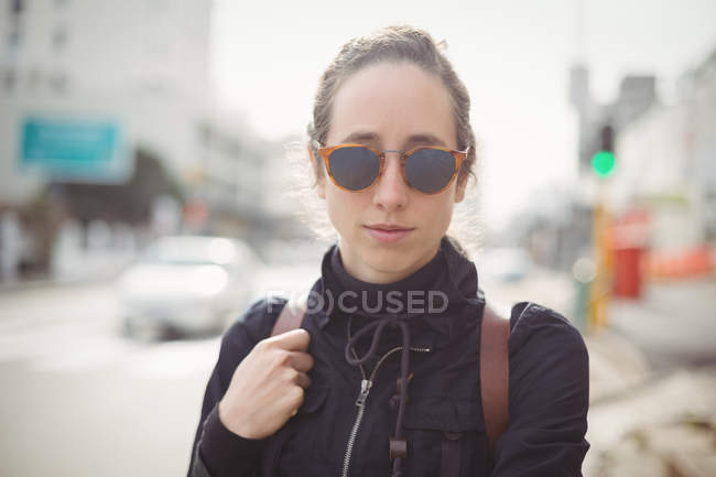 Portrait of a woman wearing sunglasses in city — Stock Photo