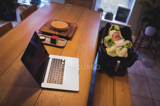 Ноутбук на дерев'яний стіл з дитиною у фоновому режимі на дому — стокове фото