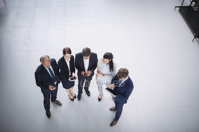 Vista aerea degli uomini d'affari che utilizzano il telefono cellulare e il tablet digitale in ufficio — Foto stock