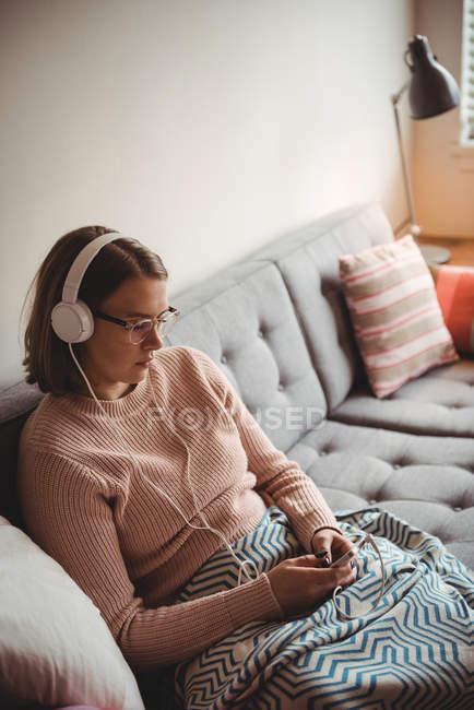 Женщина сидит на диване и слушает музыку на мобильном телефоне в гостиной дома — стоковое фото