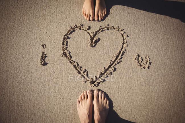 Piedi di coppia in piedi vicino ti amo disegnato sulla spiaggia — Foto stock
