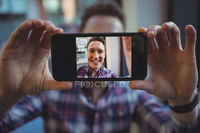 Jeune homme prenant selfie sur téléphone mobile dans la cafétéria — Photo de stock