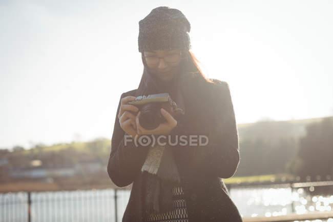 Donna che guarda le foto sulla fotocamera digitale nel parco in una giornata di sole — Foto stock