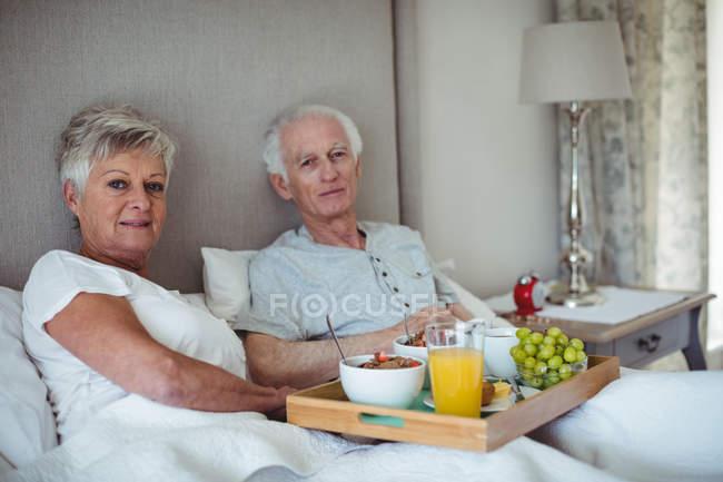 Senior pareja con bandeja de desayuno en cama en camas - foto de stock