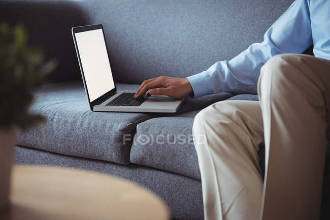 Mid section of man using laptop in living room at home — Stock Photo