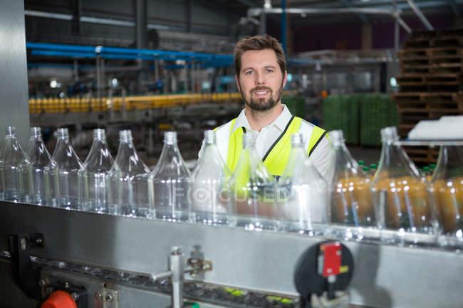 Портрет молодого мужчины, стоящего у производственной линии на соковом заводе — стоковое фото