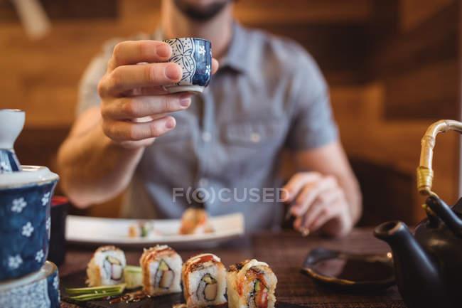 Средней части человека, показаны Кубка в ресторане — стоковое фото