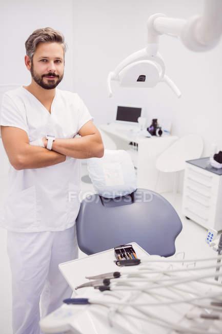 Zahnarzt steht mit verschränkten Armen in Klinik — Stockfoto