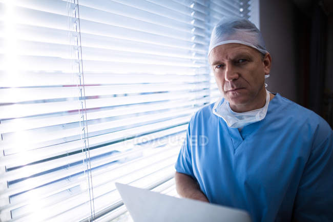 Portrait of surgeon using laptop at hospital — Stock Photo