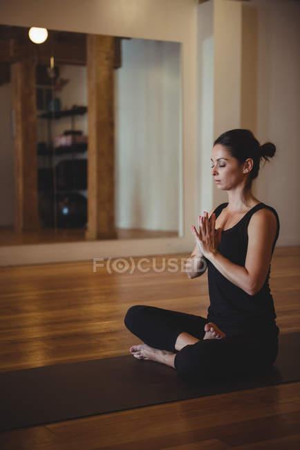 Женщина расслабляется во время занятий йогой в фитнес-студии — стоковое фото