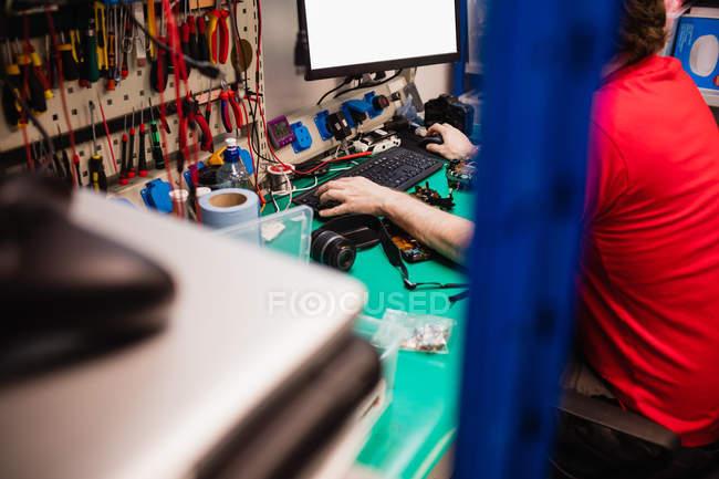 Чоловік працює на настільному ПК є центром ремонт електроніки — стокове фото