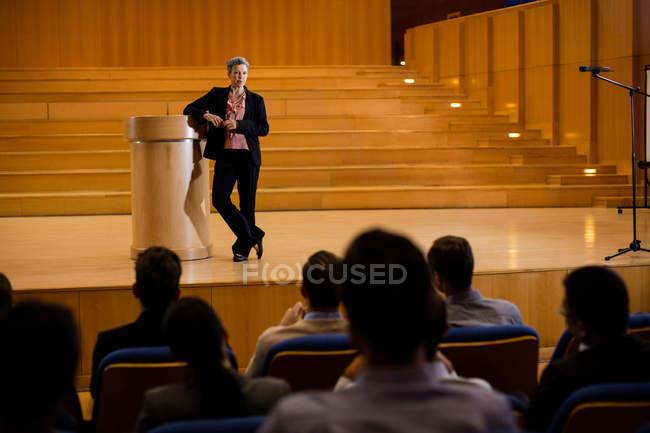 Femmina business executive tenendo un discorso al centro congressi — Foto stock