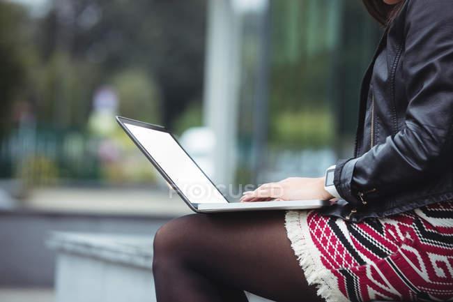 Partie médiane de la femme utilisant un ordinateur portable à l'extérieur de l'immeuble de bureaux — Photo de stock