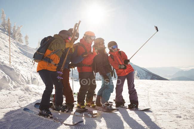 Group of skiers taking selfie on mobile phone during winter — Stock Photo