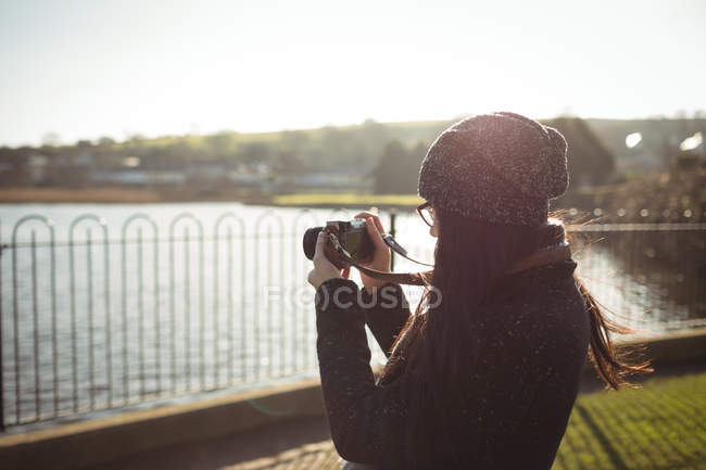Rear view of woman taking photos on digital camera — Stock Photo