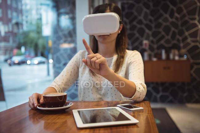 Бізнес-леді за допомогою віртуальної реальності гарнітура сидячи за столом кафе з кави, цифровий планшет і телефон — стокове фото