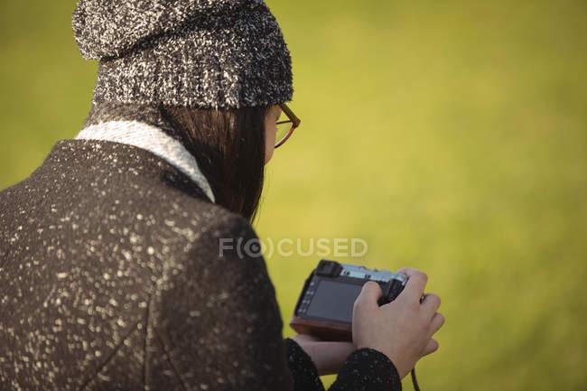 Вид сзади женщины, смотрящей на фотографии на цифровой камере в солнечный день — стоковое фото