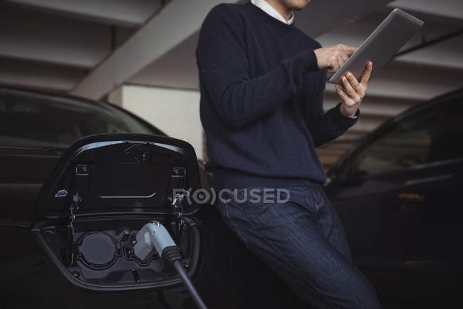 Man using digital tablet while charging electric car in garage — Stock Photo