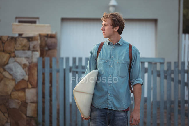 Man with backpack carrying a surfboard — Stock Photo