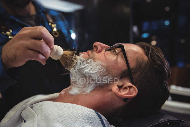 Mid section of barber applying cream on client beard in barber shop — Stock Photo