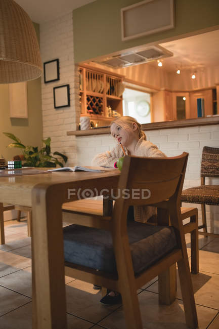 Chica pensativa, sentada en la mesa y estudiar en casa - foto de stock