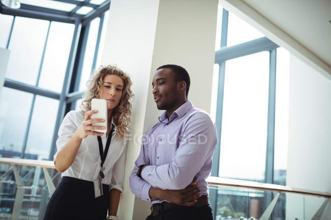 Dirigeants d'entreprises discuter au téléphone mobile dans le couloir de bureau — Photo de stock