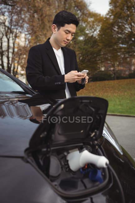 Mann benutzt Handy beim Laden von Elektroauto auf Straße — Stockfoto