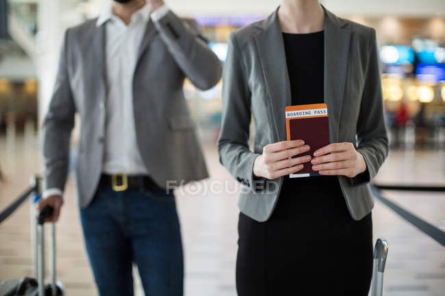 Mid section of businesspeople waiting in queue at a check-in counter with luggage in airport terminal — Stock Photo