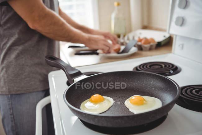 Close-up de ovos fritos em uma frigideira na cozinha — Fotografia de Stock