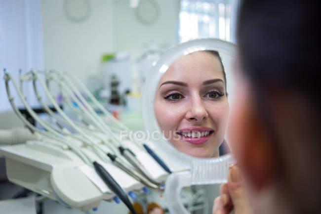 Paziente che guarda la faccia nello specchio alla clinica della pelle — Foto stock
