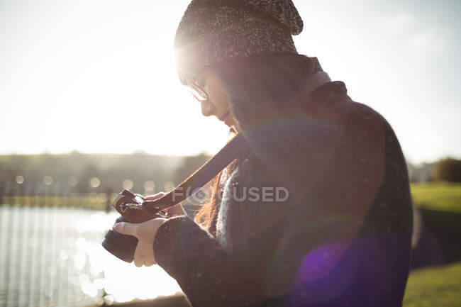 Woman looking at photos on digital camera on a sunny day - foto de stock