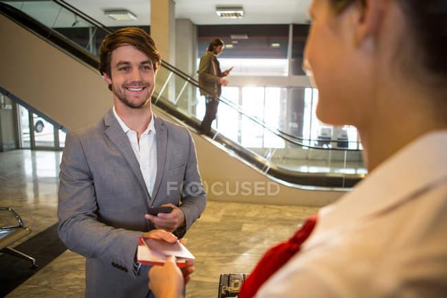 Empresario da su embarque pase a personal femenino en el check-in desk en el aeropuerto terminal - foto de stock