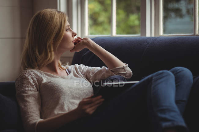 Thoughtful woman sitting on sofa with digital table in living room at home — Stock Photo