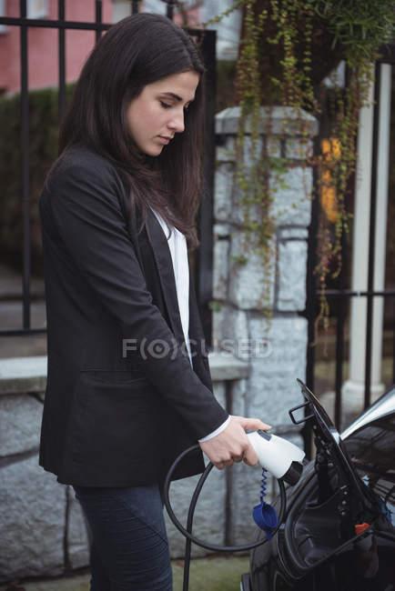 Belle femme recharge voiture électrique à la station de recharge du véhicule — Photo de stock