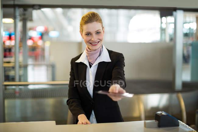 Línea aérea llegadas asistente dando pasaporte en el mostrador en la terminal del aeropuerto - foto de stock