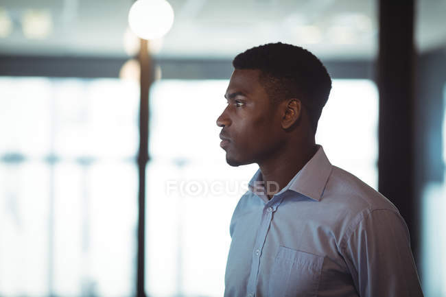 Thoughtful businessman looking away in office — Stock Photo