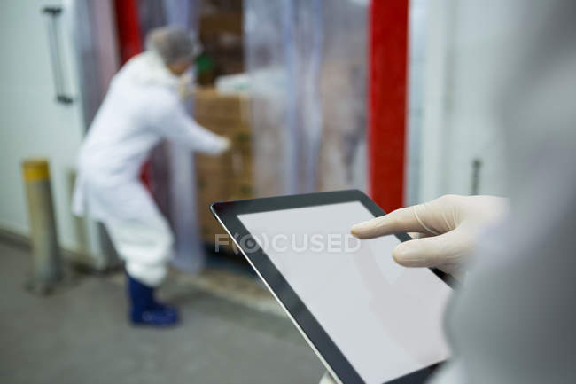 Technician using digital tablet at meat factory — Stock Photo