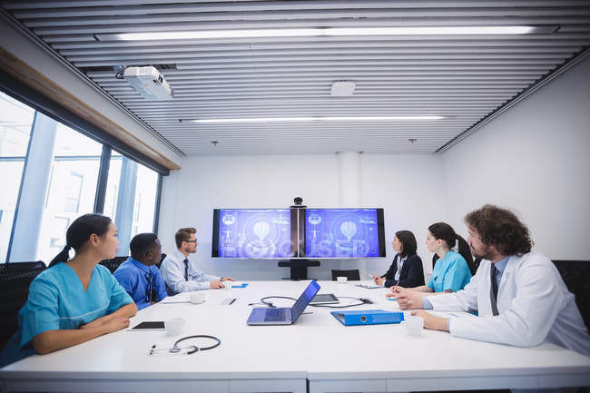 Team of doctors looking at screen in conference room at hospital — Stock Photo
