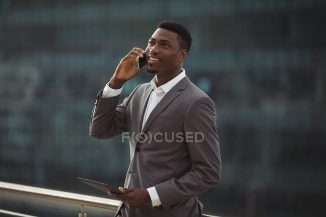 Businessman holding digital tablet and talking on mobile phone on office terrace — Stock Photo