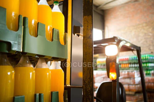 Бутылки желтого сока на вилочном погрузчике на складе — стоковое фото