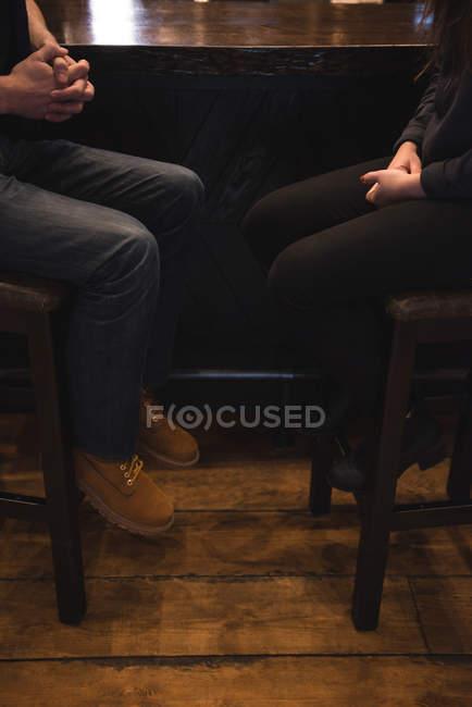 Низкая часть пары, сидящей на стульях у барной стойки — стоковое фото
