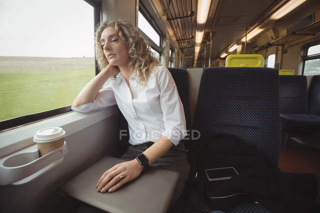Tired businesswoman sleeping in train while travelling — Stock Photo